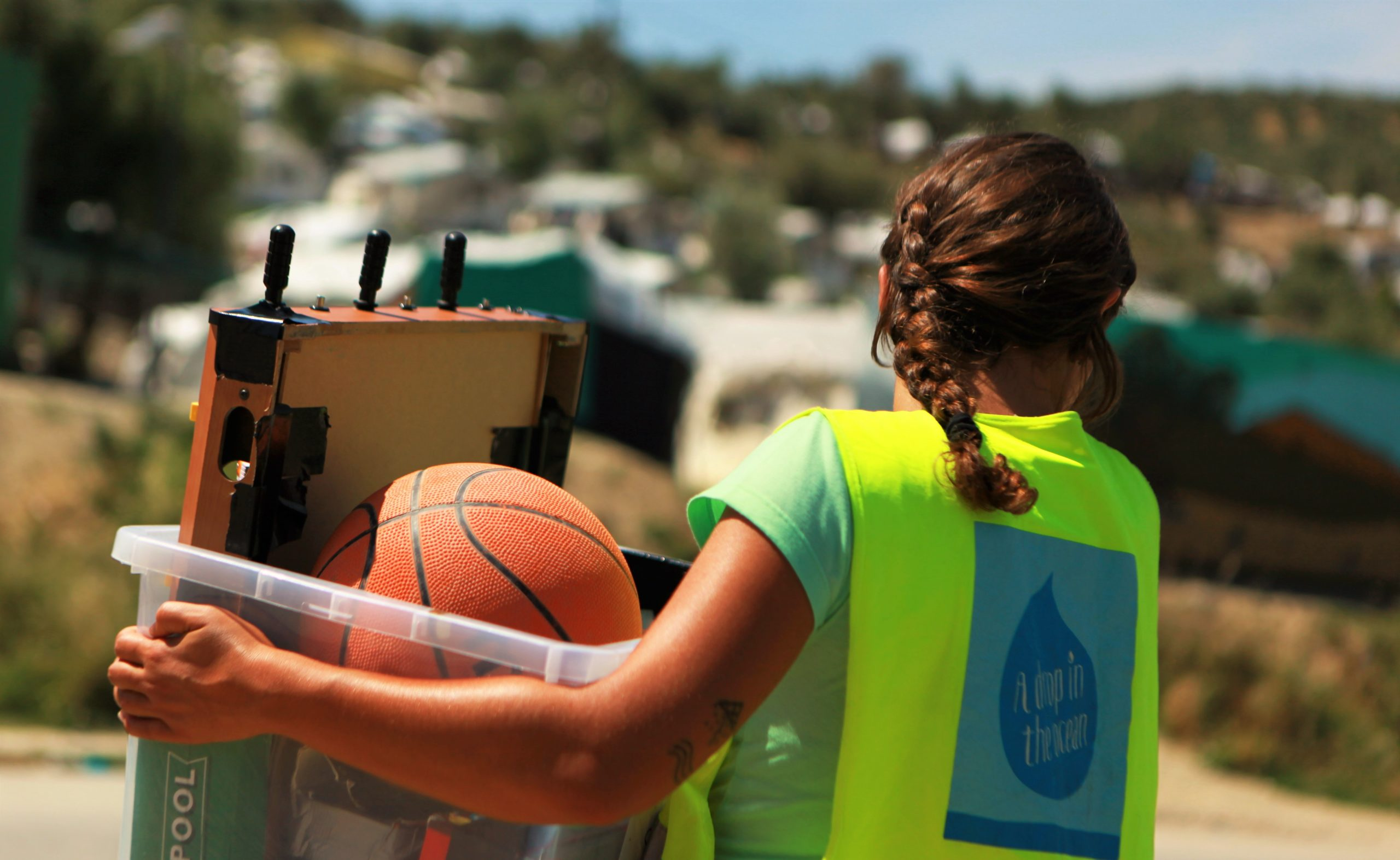 Drop volunteer bringing games for unaccompanied minors in Moria refugee camp