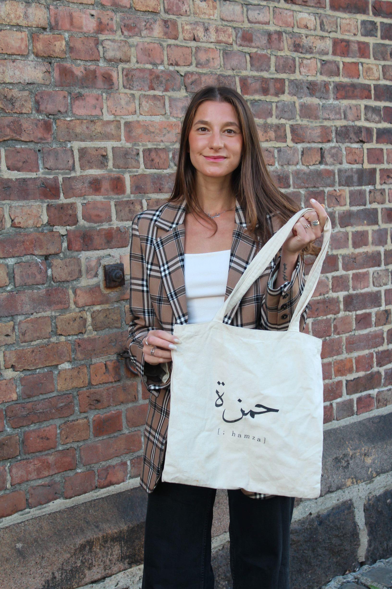 Aliaa Noelle Hamza viser frem sitt handlenett med arabiske ord